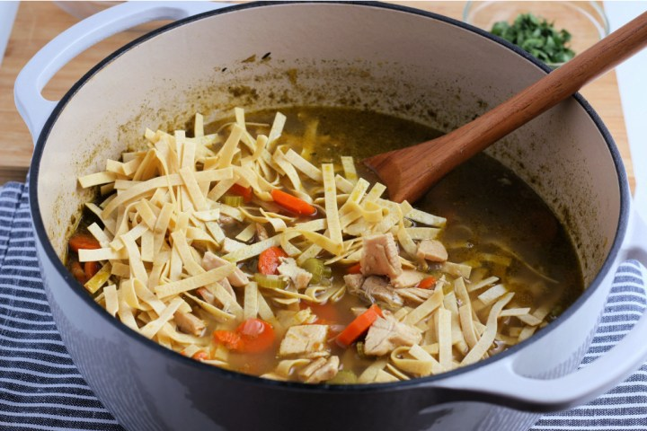 Egg noodles being added in to soup pot