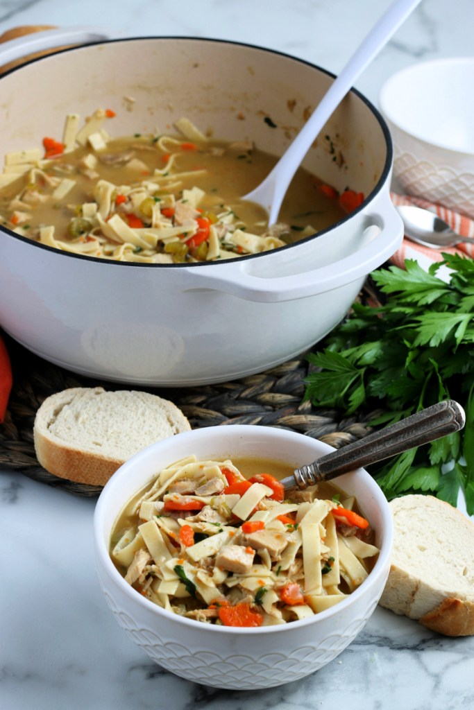 Turkey noodle soup being served in a bowl with some sliced bread