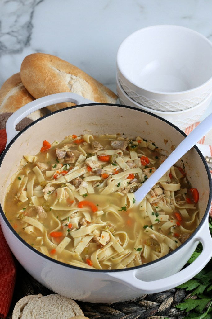 Turkey Noodle Soup in a large soup pot with a serving spoon