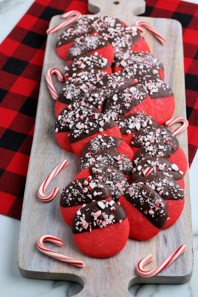 Peppermint Dipped Cookies stacked on a wooden serving board