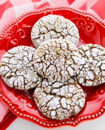 Gingerbread Crinkle Cookies stacked on a red plate