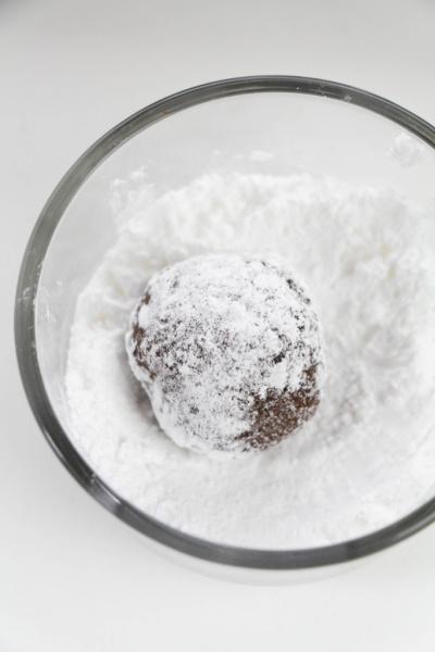 rolling dough ball in powdered sugar