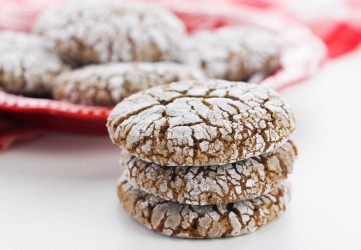 Gingerbread Crinkle Cookies stacked on a red plate and stacked next to the plate