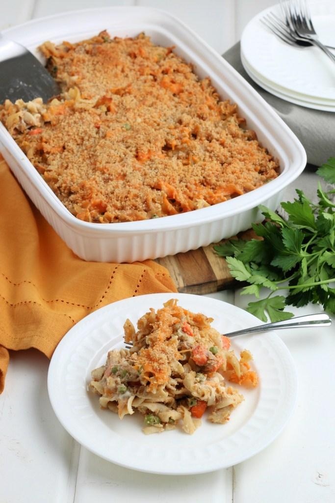 a casserole dish with tuna noodle casserole next to a plate with tuna noodle casserole on it