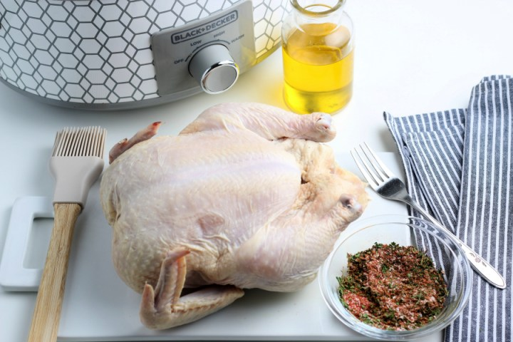 whole raw chicken next to a small bowl of seasoning