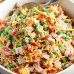 Classic Ham and Pea Salad in a serving bowl with a spoon