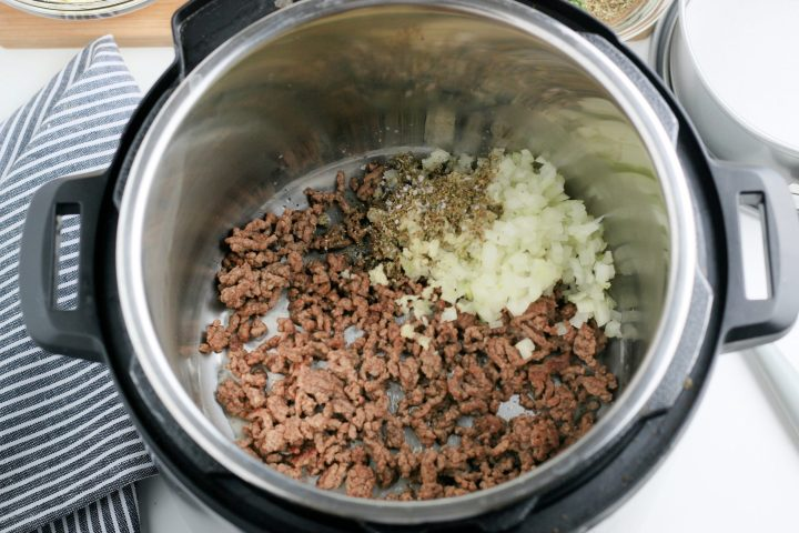 ground beef, seasoning, garlic, and onion cooking in instant pot