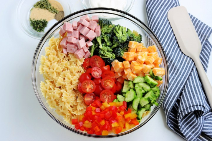 ingredients for summer bowtie pasta salad in a large mixing bowl