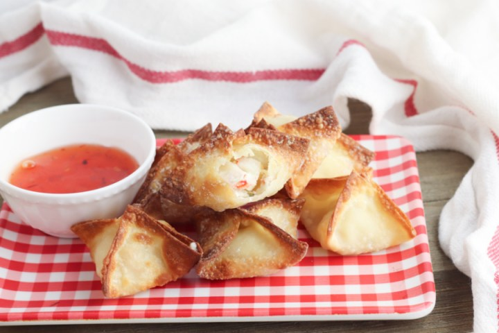 air fryer crab rangoons stacked on a plate with a small bowl of sauce