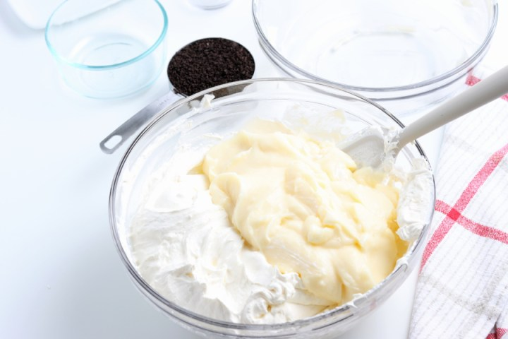 pudding mixture being mixed into whipped cream mix