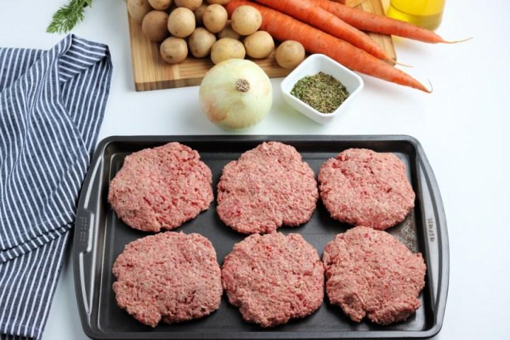 6 hamburger patties on a baking sheet