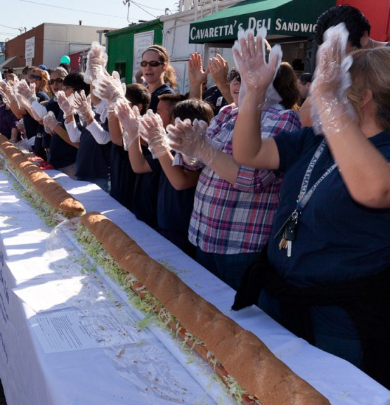 Volunteers celebrate finishing the 100 foot submarine sandwich commemorating Canoga Park's 100th anniversary at Cavaretta's Deli on Sherman Way in Canoga Park, Calif. Saturday Febrary 18, 2012. Photo by Ava Weintraub
