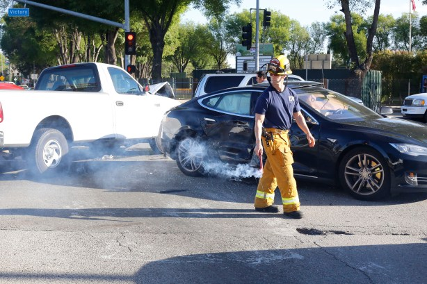 Firefighter sets flares to ward off on-coming traffic at the scene of an accident on the Victory and Winnetka intersection, at Pierce College, Woodland Hills, March 12, 2014.