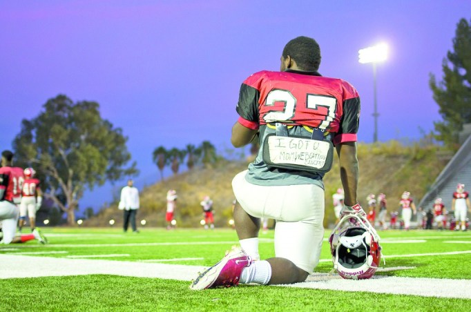 """Robert Fowlkes, a running back for Pierce College, takes a knee during practice at John Shephard Stadium of Pierce College in Woodland Hills, Calif., Oct. 22, 2014. Fowlkes' is currently fighting a rare form of cancer in her spine. """"I got U mom. We beating cancer,"""" is written on Fowlkes backplate. Photo: Nicolas Heredia"""