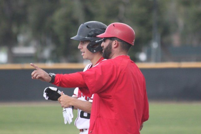 Pierce College assistant baseball coach Eric Bloom stands at first base and leads a player during a game against Ventura College on Tuesday, March 4. Photo by: Megan Moureaux