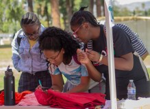 (Left to right) Savannah Booker, Jaden Williams and Saidou Toni Nouia stand around Williams (center) as she writes her message on a shirt during the Clothesline Project on Oct. 16, 2019 in Rocky Young Park at Pierce College in Woodland Hills, Calif. Hosted by ASO, the Diversity Committee and B.R.A.V.E., this event brings awareness to survivors of abuse by displaying messages or stories written by students. Photo by Angelica Lopez.