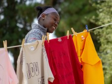 Jane Benga hangs up her friend's shirt that has a message for survivors of abuse during the Clothesline Project on Oct. 16, 2019 in Rocky Young Park at Pierce College in Woodland Hills, Calif. Hosted by ASO, the Diversity Committee and B.R.A.V.E., this event brings awareness to survivors of abuse by displaying messages or stories written by students. Photo by Angelica Lopez.