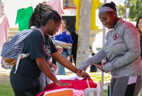(Left to right) Ngo Mbok Toni Saidou Noura talks to Jane Benga while picking a shirt during The Clothesline Project, a domestic violence awareness event at Rocky Young Park at Pierce College in Woodland Hills, Calif., on Oct. 16, 2019. Photo by Cecilia Parada.