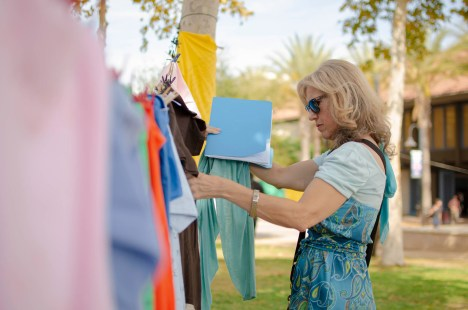 Barbara Anderson, Pierce Academic Senate President, stretches a shirt to read the words written on it at Rocky Young Park during the Clothesline Project on Wednesday, October 16, 2019, in Woodland Hills, Calif. (Photo by Kevin Lendio)