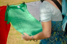 Barbara Anderson, Pierce Academic Senate President, reads the hand-written words printed on a shirt at Rocky Young Park during the Clothesline Project on Wednesday, October 16, 2019, in Woodland Hills, Calif. (Photo by Kevin Lendio)