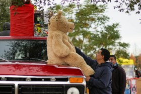 David Quintanila puts a teddy bear on a Ford pickup truck at Motor 4 Toys at Pierce College's Parking Lot 7 in Woodland Hills, Calif. on Dec. 1, 2019. Photo by Cecilia Parada.