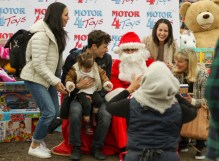 Families pose for photos with Santa Claus at Motor 4 Toys at Pierce College's Parking Lot 7 in Woodland Hills, Calif. on Dec. 1, 2019. Photo by Cecilia Parada.
