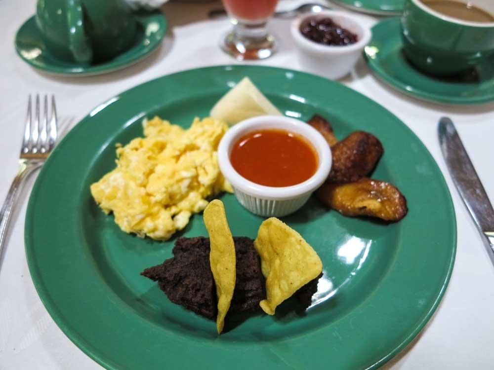 guatemalan breakfast with eggs, sausage, beans and sauce