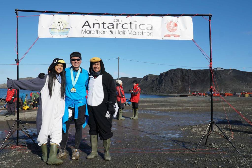 The Antarctica Marathon Finish line. Halef with two people dressed as penguins