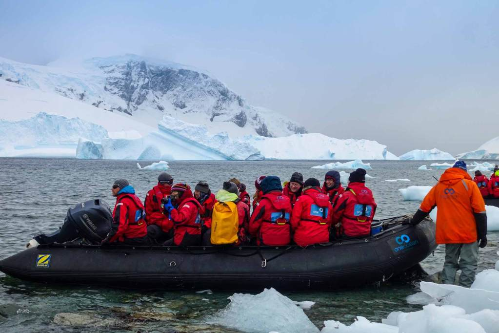 a group of expeditioners on a zodiac (with a couple in the water pushing the boat)