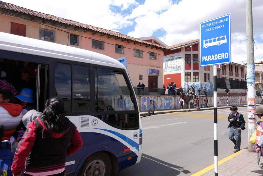 A cusco bus stop with passengers boarding a combi.