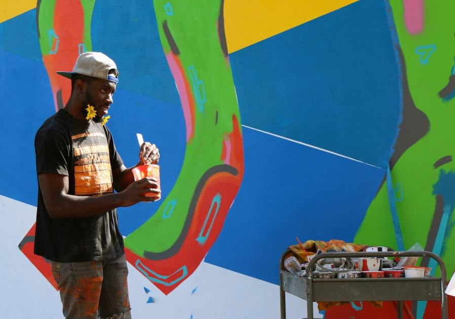 Josiah Ihem, 23, a fine arts major, paints a mural on the wall facing Alumni Park on Oct. 22. He is one of a few students who have created art around campus. The mural represents various majors to show how they interact with each other. Photo by Diana Olivares/The Runner
