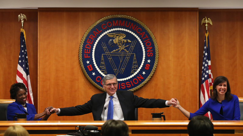 At the start of a meeting to decide the issue of net neutrality, Federal Communications Commission Chairman Tom Wheeler (center) holds hands with FCC Commissioners Mignon Clyburn (left) and Jessica Rosenworcel at the FCC headquarters Thursday. Mark Wilson/Getty Images