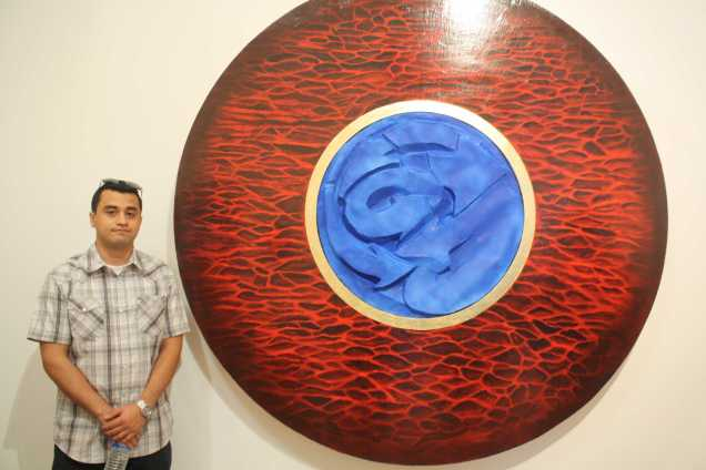 """Jose Bravo posing next to his art work """"Lil Bit of Rock n' Roll, Lil' bit of Hip Hop, and Lil' bit of Japan during the opening of Nexus senior art exhibition on Thursday, May 14 at Todd Madigan Gallery"""