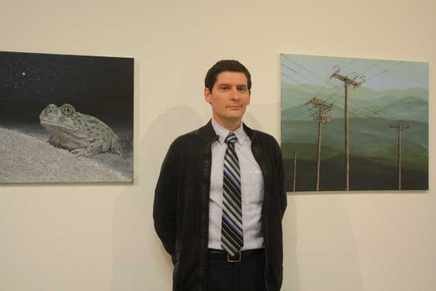 """Derek Ryan Posing for the camera with his paintings """" Stars"""" (Left) and """"Hillside"""" (Right) at the opening of Nexus senior art exhibition on Thursday, May 14 at Todd Madigan Gallery"""