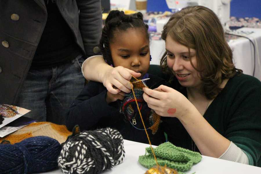 : Elizabeth Lewis teaching 3-year-old Lula Wyatt how to knit at the Maker Faire on Saturday.  By Alejandra Flores/ The Runner
