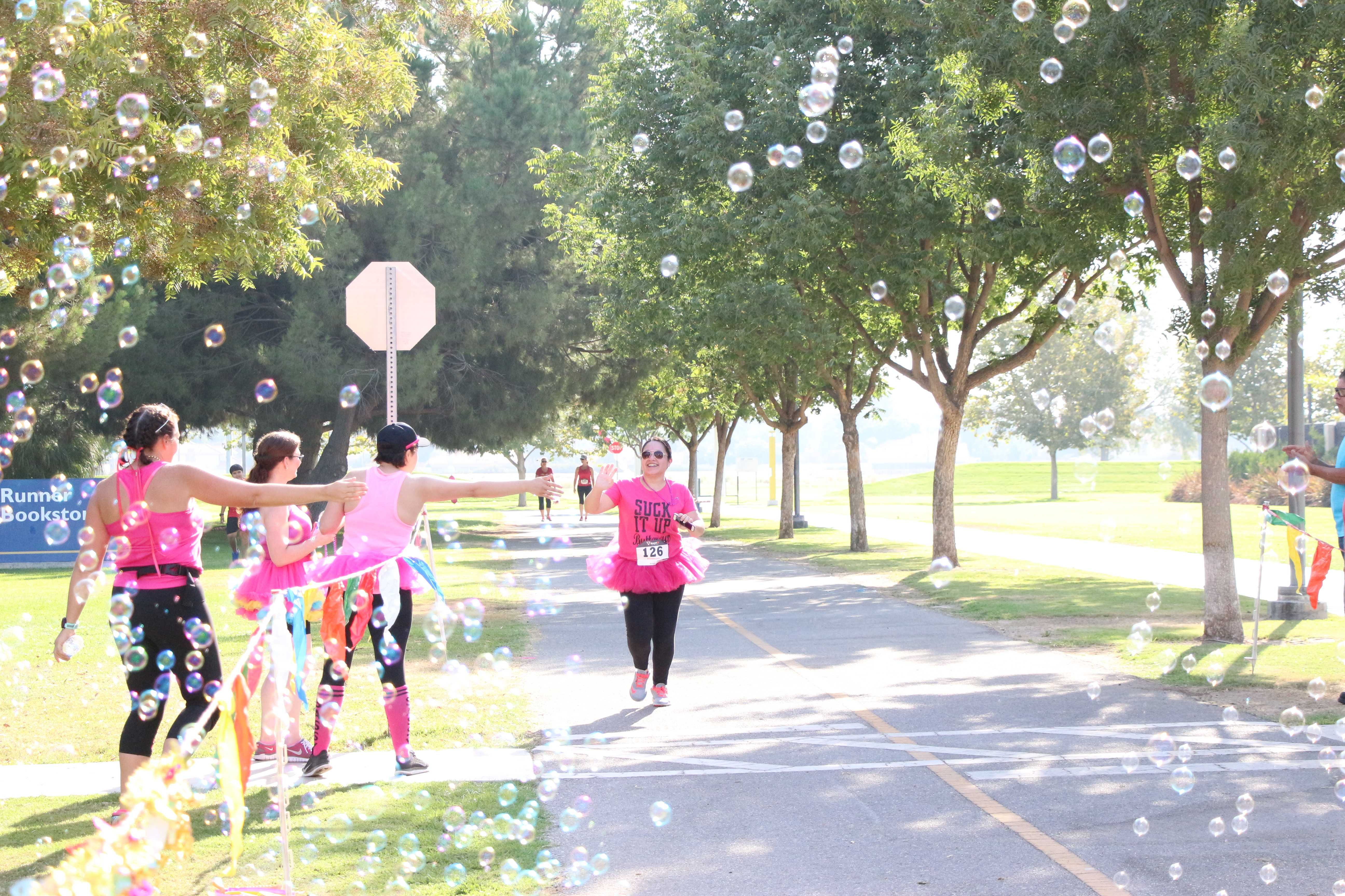 Participants in tutus high-fiving their teammate as she is reaching the finish line of the 5K Fun Run course benefitting the organization Dress for Success on Saturday at CSUB. Photo by Alejandra Flores/ The Runner