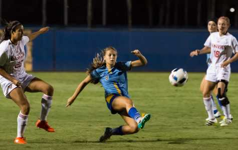 CSU Bakersfield's Sophie Freeman slides to a kick at Friday night's game as Johanna Di Lulo and Alexis Stephenson look on.  Ben Patton/ The Runner