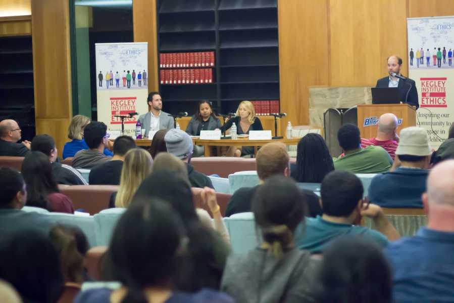Photo by Scott Swan / The Runner Dr. Nate Olson (standing) moderates the discussion on Free Speech. Panelists from left to right are Dr. Michael Burroughs, Dr. Ivy Cargile, & Dr. Jeanine Kraybill.