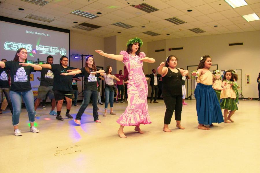 Andrea Herskowitz, from the Tatou Uma dance school of Bakersfield, brings the crowd together to teach them the basics on Polynesian dancing on Mar 9 in the Student Union Multi-Purpose Room.