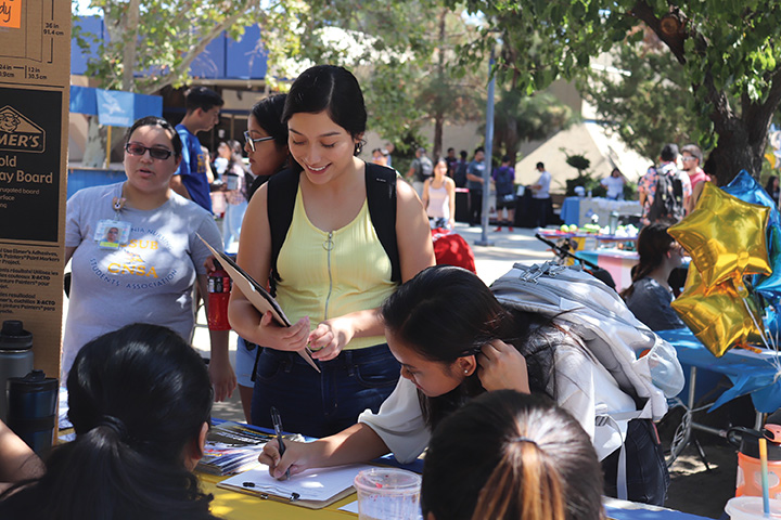 Students interact with the M.E.Ch.A. club leaders at the Club Fair on Sept. 4 outside the Runner Cafe.