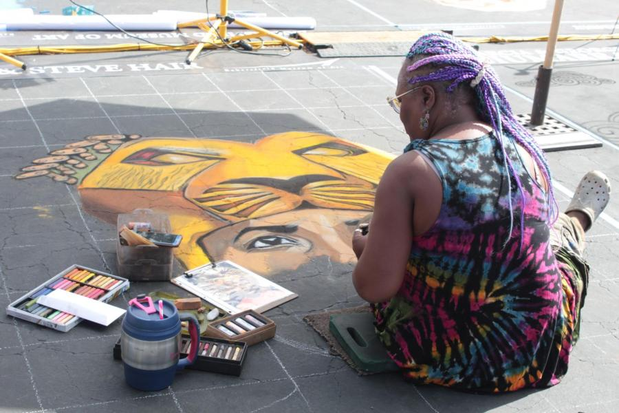Artist Lori Antoinette works on her piece on Day 1 of Via Arté at the Market Place.