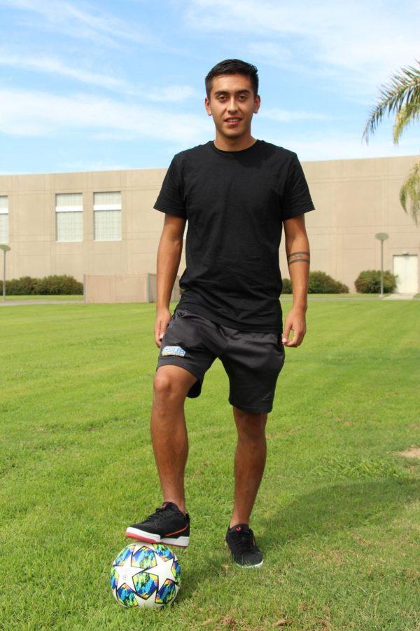 Carlos Armendariz, sophomore midfielder, poses with soccer ball near the main soccer field.