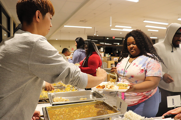 On Nov. 20, 2019, international student, Hikaru Sumie, is seen serving a Japanese cuisine to students at the Runner Café during the International Food and Culture Show.