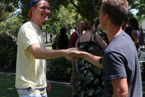 Tim Ulitzka a German mechanical engineering student shakes hands with fellow German Hanes Kolasch a business administration student at talk time for the international students on campus on Sept. 3, 2019.
