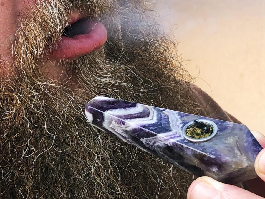 A marijuana consumer exhales smoke on April 20.