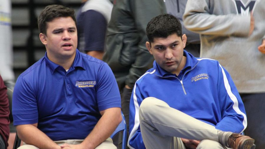 Interim wrestling coach Luke Smith, left, sits next to former coach Manny Rivera during a match last season.