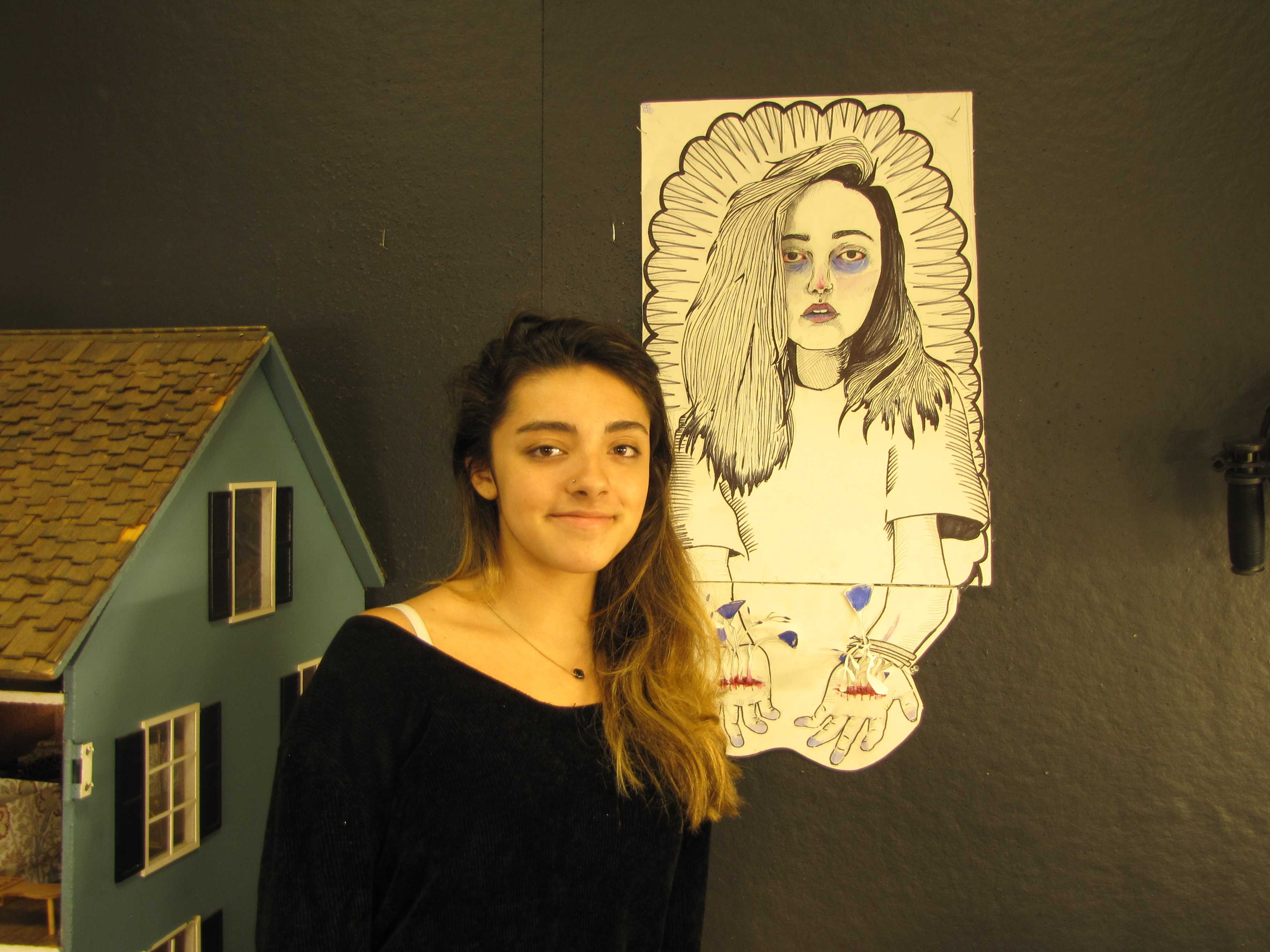 Photo by Hannah Lowenstein. Junior Logan Roche with her self-representation from the MassArt program.