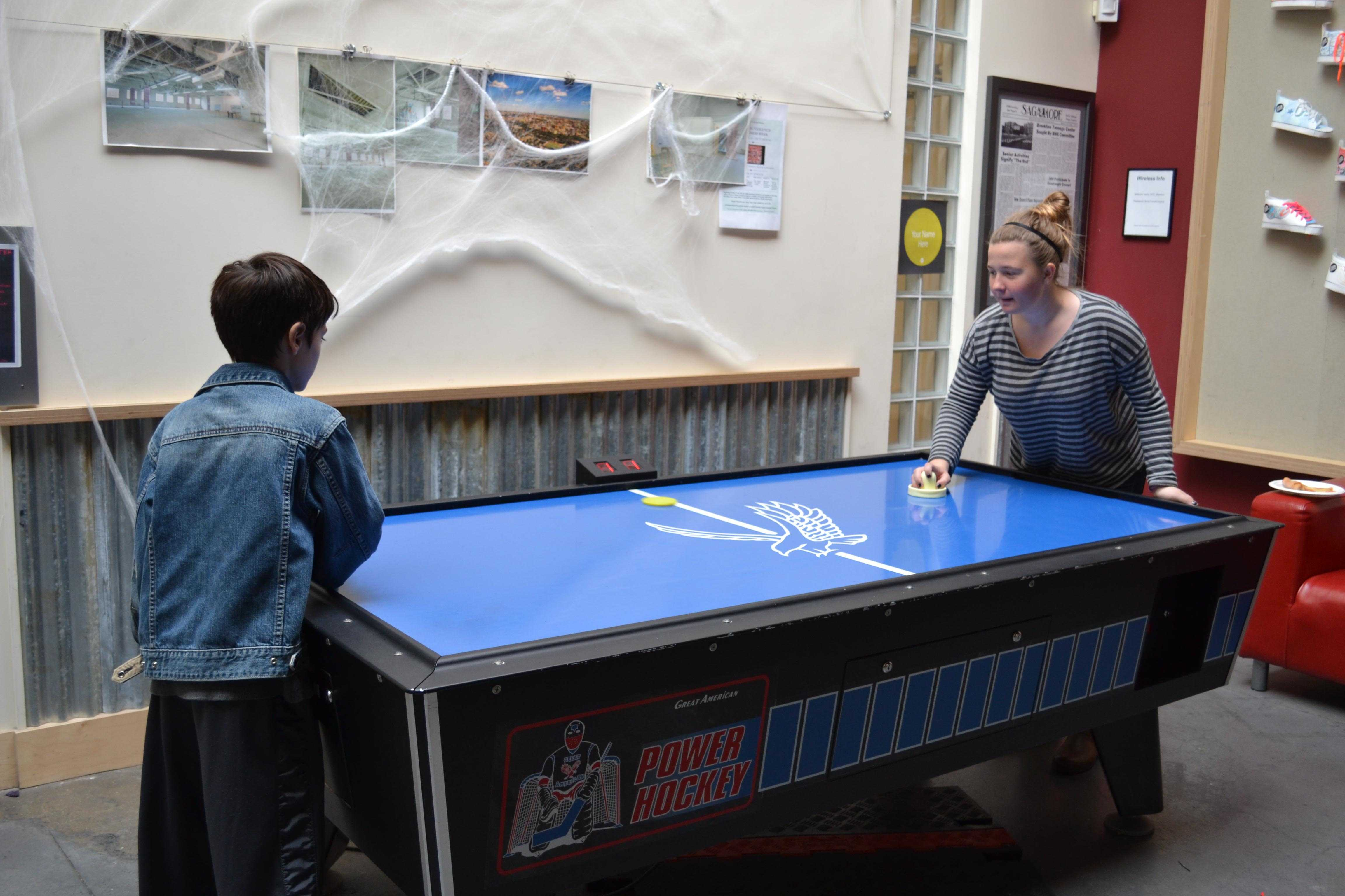 Brookline Tutor-Mentor Bridget McMahon plays air hockey with her middle school-aged tutee. Tutor-mentors and tutees often meet at the Brookline Teen Center for an hour and a half on Sundays.