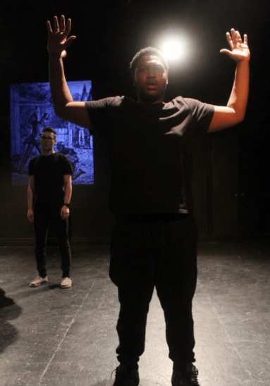 Junior Anthony Saunders stands with his hands raised as he is accosted by senior Sam Pollak, who is playing a cop. Take during the segment of the plays titled