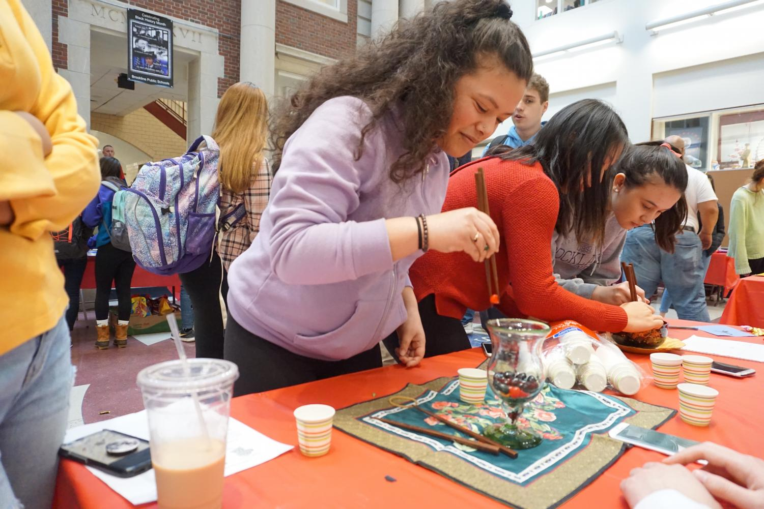 With her eye on the prize, sophomore Kaisa Sazama-Framil concentrates intently to land a slippery jelly bean in a paper cup. Students were timed to see who could move the most jelly beans from the glass with chopsticks.